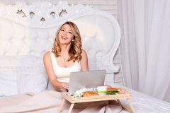 Young pretty blond woman sitting on bed with laptop having breakfast, freelancer or blogger at home. Woman works on royalty free stock photography