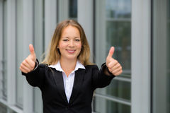 Young pretty blonde business woman showing thumbs up Royalty Free Stock Image