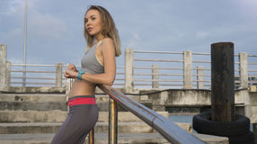 Young pretty blonde female wearing exercise clothing standing on the pier near the sea and enjoying early morning. Royalty Free Stock Images