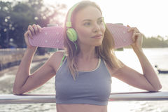 Young pretty blonde fitness female wearing bright green headphones listening music and holding pink skateboard while standing on t Royalty Free Stock Images