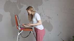 Young pretty blonde girl with brush and palette standing near easel drawing picture. Art, creativity. Young pretty blonde girl with brush and palette standing stock footage