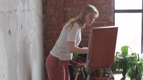 Young pretty blonde girl with brush and palette standing near easel drawing picture. Art, creativity. Young pretty blonde girl with brush and palette standing stock video footage