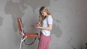 Young pretty blonde girl with brush and palette standing near easel drawing picture. Art, creativity. Young pretty blonde girl with brush and palette standing stock video