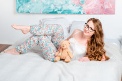 Young pretty blonde girl in pajamas on the bed in his room and h Royalty Free Stock Photos