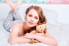 Young pretty blonde girl in pajamas on the bed in his room and h Royalty Free Stock Photo