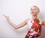 Young pretty blonde girl presenting something at Royalty Free Stock Images
