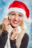 Cute Christmas Girl. Young pretty blonde girl with santa hat on her head, smiling looking at camera and tucking it into her scarf Stock Image