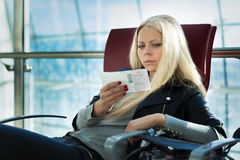 Young pretty blonde woman with air travel tickets sitting Stock Photo