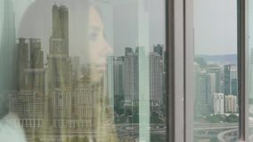 The woman Looks Through a Window. Young pretty blonde woman looks through a window at a city. Happy attractive girl stock footage