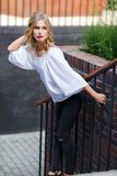 Young pretty blonde woman posing on staircase outdoors Stock Photography