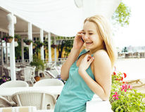 Young pretty blonde woman after shopping sitting at cafe outside on street smiling happy talking on phone, lifestyle. People concept close up Stock Image