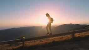Woman walks on mountain pass on sunset stock video footage