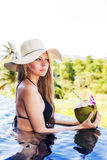 Young pretty blonde woman in swimming pool with coconut coctail Stock Photos
