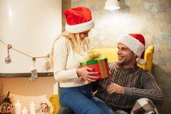 Young pretty blonde woman in Santa`s hat giving present to her h Royalty Free Stock Image