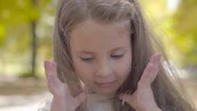Young pretty brown-eyed girl with long brunette hair smiling to the camera. Close-up of charming caucasian child. Standing in the autumn park stock video footage