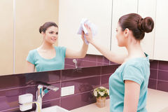 Young pretty brunette cleaning tap Royalty Free Stock Photos