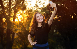 Young pretty brunette doing selfie in Prak on nature background.  Royalty Free Stock Photo