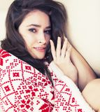 Young pretty brunette girl in Christmas ornament blanket getting Stock Photos