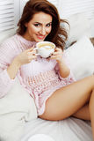 Young pretty brunette girl laying in cozy bed with coffee wearing wool winter sweater happy smiling, lifestyle people Royalty Free Stock Image