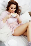 Young pretty brunette girl laying in cozy bed with coffee wearing wool winter sweater happy smiling, lifestyle people Stock Image