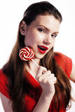 Young pretty brunette girl with red candy posing Royalty Free Stock Photography