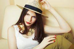 Young pretty brunette girl wearing hat and sunglasses waiting alone at home, lifestyle people concept royalty free stock images