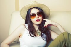 Young pretty brunette girl wearing hat and sunglasses waiting alone at home, lifestyle people concept stock photos