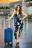 Young pretty brunette. Posing at the airport standing next to a suitcase dressed in a long dress royalty free stock images