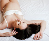 Young pretty brunette pregnant woman laying in bed on white shits interior, lifestyle people concept tenderness Royalty Free Stock Photography