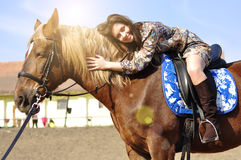 Young pretty brunette riding and caressing her horse outdoor.  Stock Photo