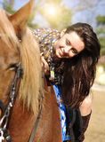 Young pretty brunette riding and caressing her horse outdoor.  Stock Photos