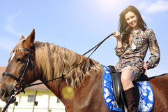 Young pretty brunette riding horse and holding reins outdoor. Young pretty brunette riding horse and holding reins outdoor Royalty Free Stock Images