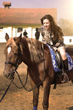 Young pretty brunette riding horse outdoor Royalty Free Stock Photos
