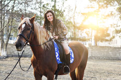 Young pretty brunette riding horse outdoor.  Royalty Free Stock Photography