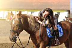 Young pretty brunette riding horse outdoor.  Royalty Free Stock Images