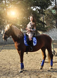 Young pretty brunette riding horse outdoor Stock Photo