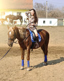 Young pretty brunette riding horse outdoor Royalty Free Stock Images