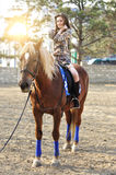 Young pretty brunette riding horse outdoor.  Stock Images