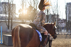 Young pretty brunette riding horse outdoor. Sun rays light the hair. Stock Image
