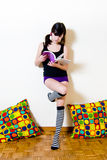 Young pretty brunette standing and reading a book with purple co Stock Photos