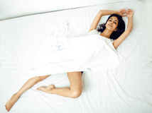 Young pretty brunette woman in bed Royalty Free Stock Image