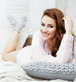 Young pretty brunette woman in her bedroom sitting at window, ha Royalty Free Stock Photography