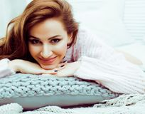 Young pretty brunette woman in her bedroom sitting at window, ha Royalty Free Stock Image