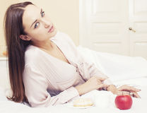 Young pretty brunette woman laying in bed, luxury Royalty Free Stock Photography