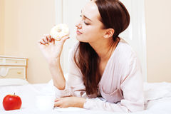 Young pretty brunette woman laying in bed, luxury white interior Royalty Free Stock Photography