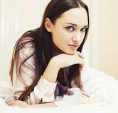 Young pretty brunette woman laying in bed, luxury white interior vintage having breakfast cute royalty free stock photos