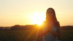 Young pretty brunette woman meditates in nature, in the field during beautiful sunset with lense flare effects Stock Photography