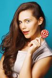Young pretty brunette woman posing happy cheerful on blue background with candy, lifestyle people concept royalty free stock image