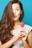 Young pretty brunette woman posing happy cheerful on blue background with candy, lifestyle people concept stock photography