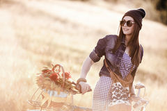Young pretty brunette woman posing. On the nature with bike in summer sunshine. Fashion portrait Royalty Free Stock Photos